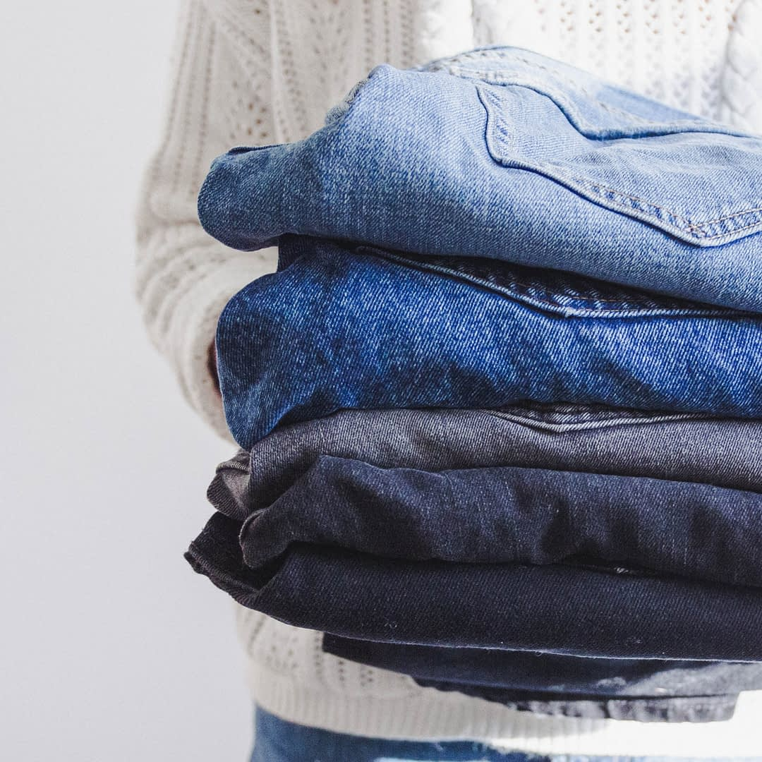 Woman holding a stack of folded jeans